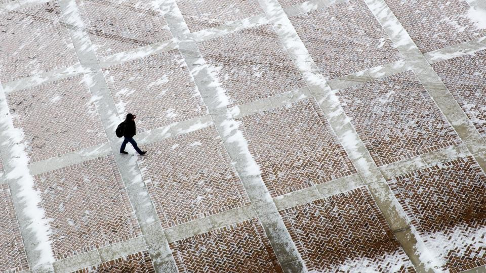 A UNL student walks through a snowy plaza on the east side of Memorial Stadium on Feb. 25. Al Dutcher, the state climatologist, said the winter was the 18th driest since 1896. (Craig Chandler | University Communications)