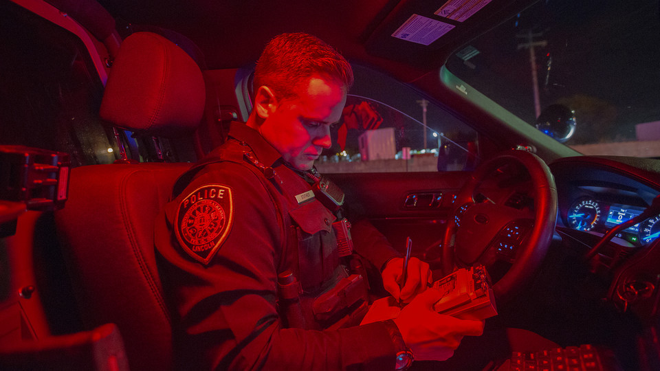 Officer Chadd Stutheit of the University Police Department writes a warning ticket during a traffic stop on Oct. 19.