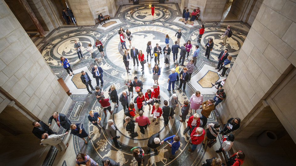 "University of Nebraska students, supporters and alumni talk to state senators in the Rotunda Gallery during ""I Love NU"" Advocacy Day 2019 at the Nebraska State Capitol."
