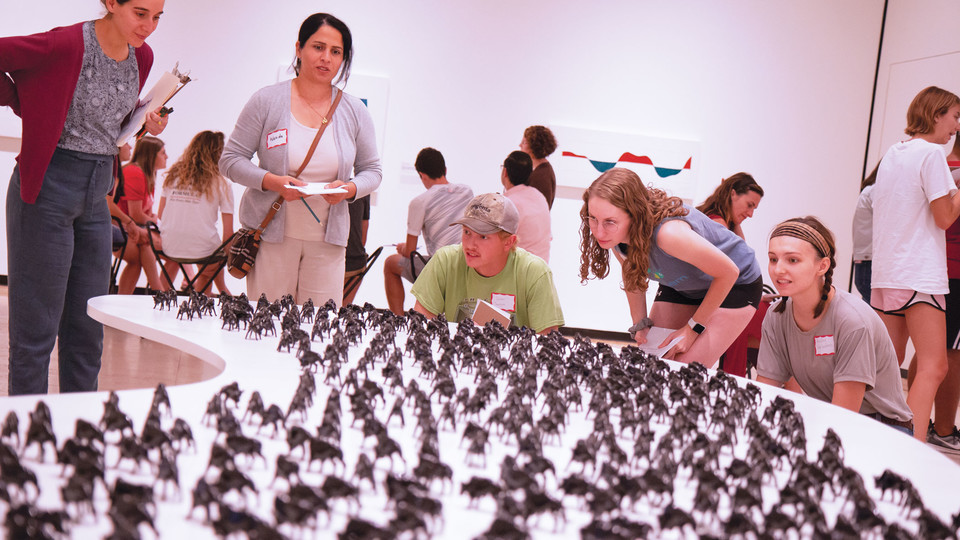 """Student and Yazidi participants inspect part of the """"Unquiet Harmony: The Subject of Displacement"""" exhibit at the Sheldon Museum of Art."""