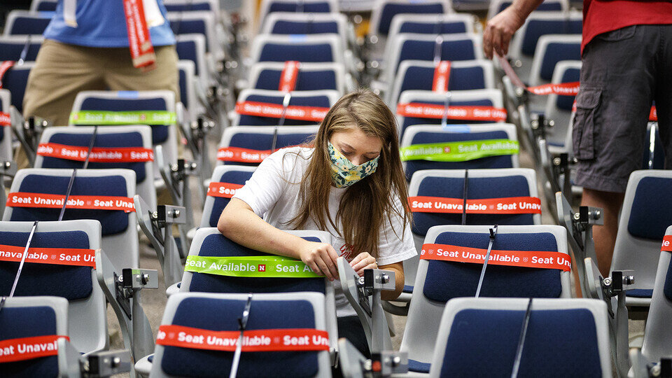 Maddie Huppert, a student worker in the Office of the Executive Vice Chancellor, wraps a green band on an available seat in a Louise Pound Hall lecture space. The bands are flexible so they do not need to be removed when the student sits down.