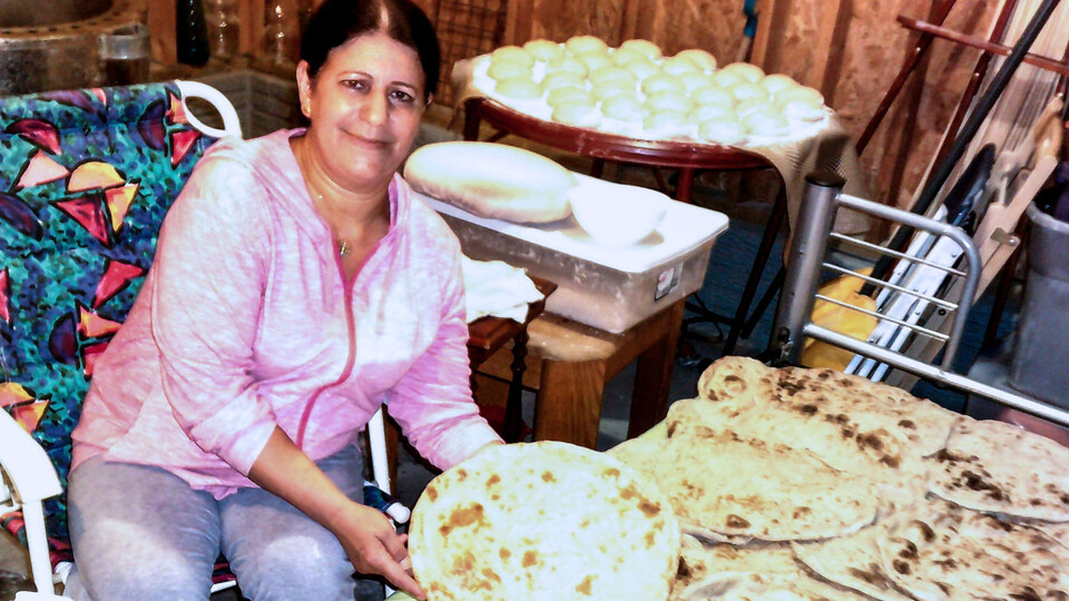 A Yazidi woman shows off a large batch of naan, a round, flat, leavened bread. In keeping with cultural traditions, many women share freshly prepared naan with their neighbors, including Americans. (Photo courtesy of Zozan Bashar)