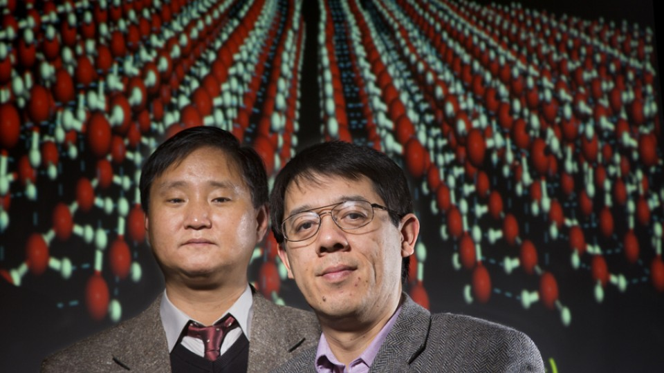 Jaeil Bai (left) and Xiao Cheng Zeng. Projected behind them is a computer model of the square nanotube array, a new two-dimensional ice form they discovered.