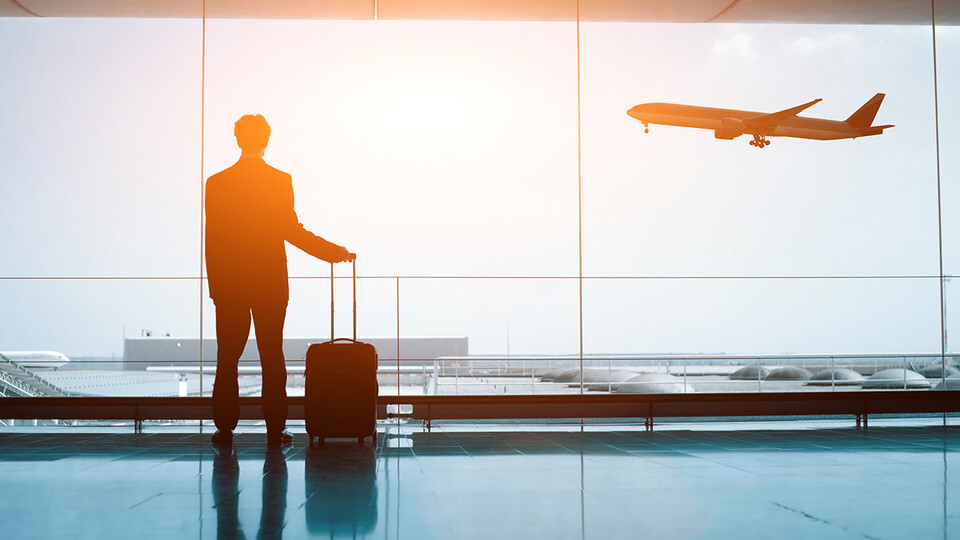Silhouette of a man standing in airport, hand on suitcase, watching an airplane land.