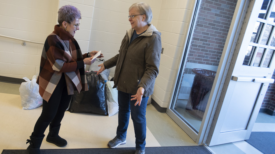 Dee Ebbeka hands Linda Kern, of Clinton Elementary School, the last of the Caring for Clinton donations Dec. 6, 2019, at the school on Holdrege Street.