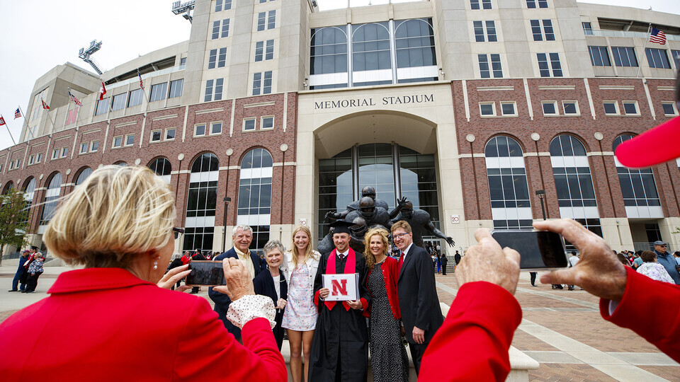 A family pauses outside the east side of Memorial Stadium to shoot graduate photos after the first commencement ceremony on May 8. The baggie of $200 in cash dropped on the south side of the stadium was found in the East Stadium parking lot by the family