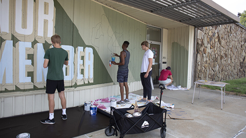 Students from Associate Professor of Art Sandra Williams' University Honors seminar Graffiti Revolution help Shawn Dunwoody (second from left) paint his mural at the Veterans of Foreign Wars at 2431 N. 48th St. Photo by Eddy Aldana.