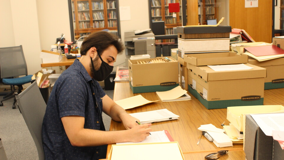 Jake Borgmann, senior, works in the Archives & Special Collections processing the Mark Awakuni-Swetland Papers.