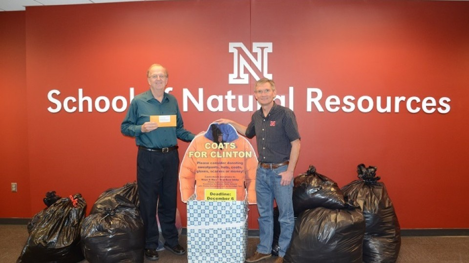 """Ken Dewey (left) and SNR director John Carroll with the """"Coats for Clinton"""" donations."""