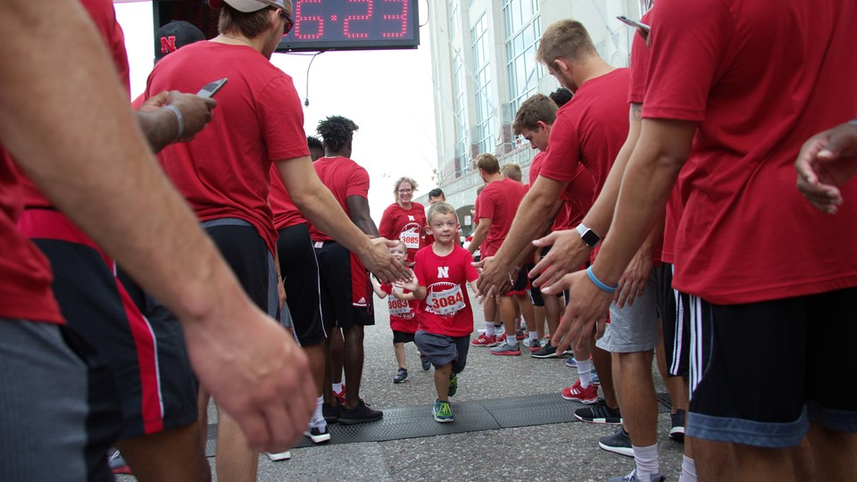 Nebraska athletes greet participants in the Nebraska Football Road Race. The seventh-annual event is July 14.