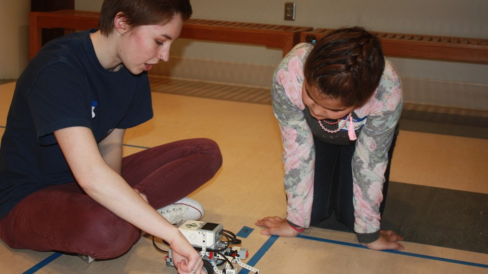 Computing for All member Allison Buckley helps a Girl Scout program a robot at last month's Girl Scout camp.