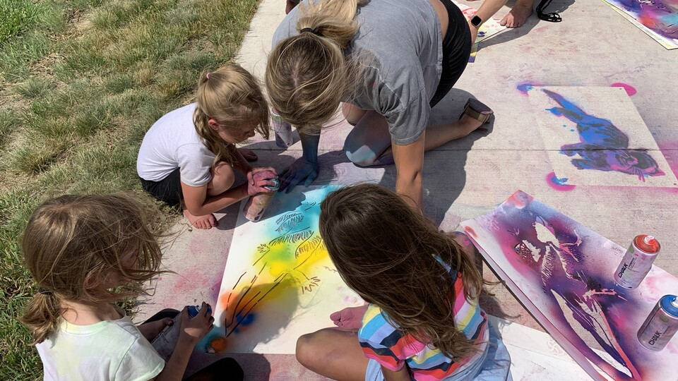 Students from the Alliance Recreation Center create spray chalk animals as part of the Stay Wild community arts project, led by Associate Professor of Art Sandra Williams.