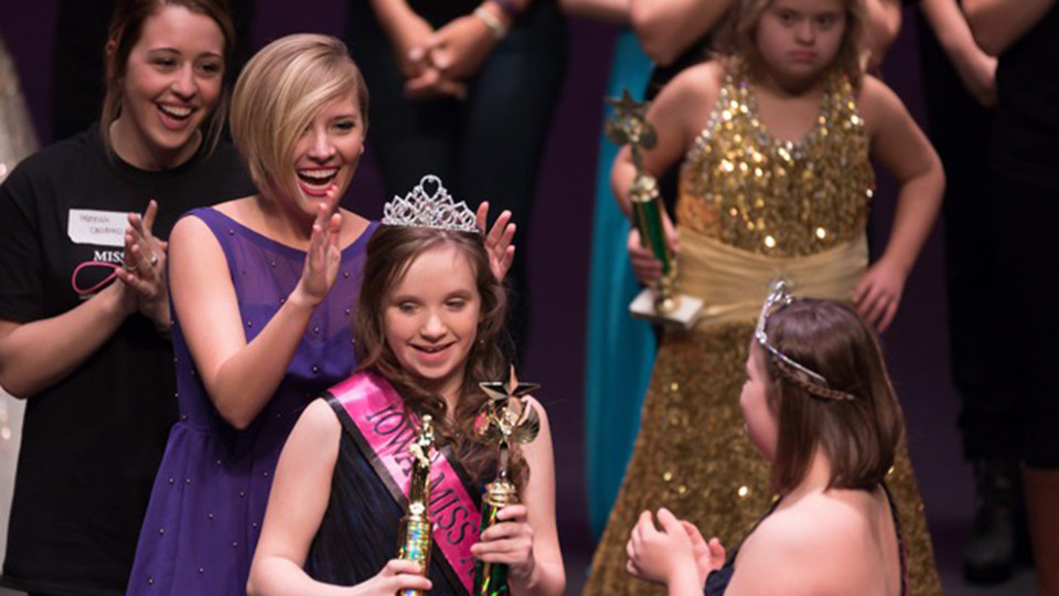 Maddie Lorenzen, a senior speech-language pathology major, crowns a queen at the Iowa Miss Amazing Pageant.