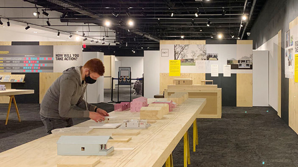 A student helps set up the NEw Attainable House exhibit