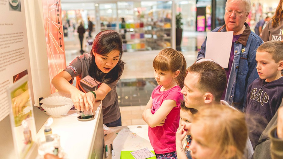 UNL student explains nanoscience to youth at 2014 NanoDays in Lincoln's Gateway Mall.