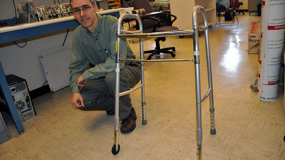 "Carl Nelson displays a walker device that finished among the top devices entered in the 2014 Design of Medical Devices Conference ""Three-in-Five"" competition."