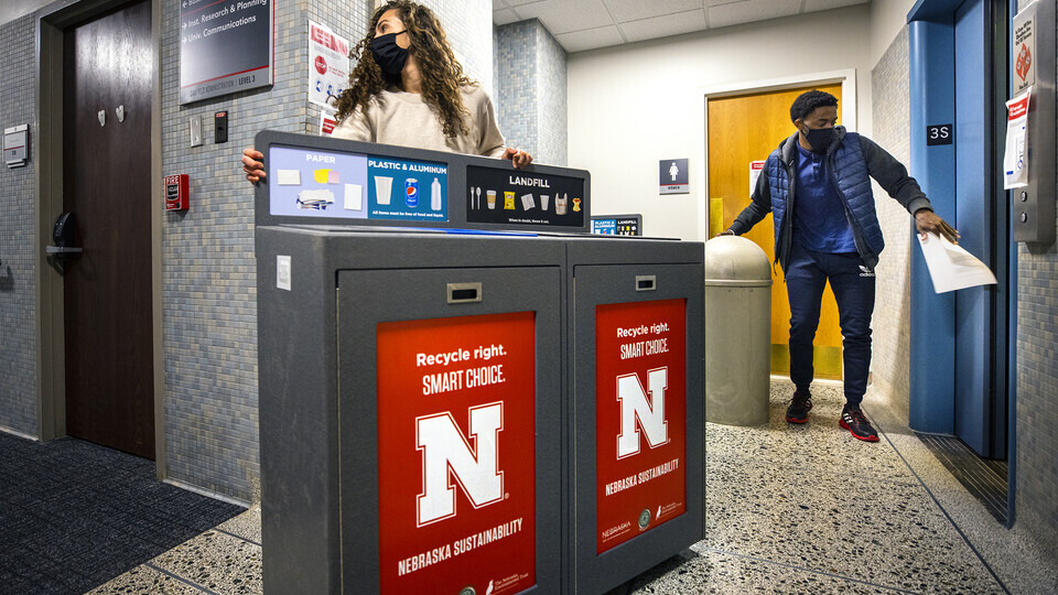 Morgan Hartman, project coordinator for recycling services, wheels a new recycling station down the hallway of Canfield Hall as student worker Damien Niyonshuti loads an old trash can onto an elevator. The Office of Sustainability is installing the new re