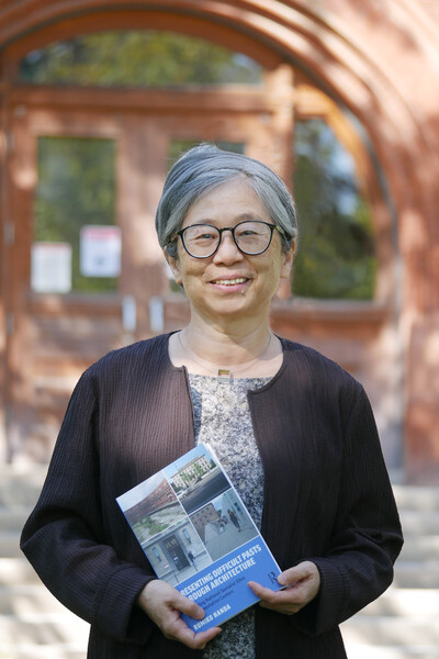 """Rumiko Handa poses with her new book """"Presenting Difficult Pasts Through Architecture: Converting National Socialist Sites to Documentation Centers"""""""