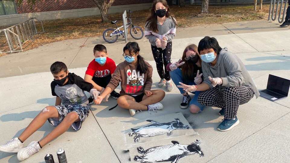 """Students at Park Middle School created spray chalk animals such as this penguin from stencils as part of the """"Stay Wild"""" community arts project, led by Associate Professor of Art Sandra Williams."""