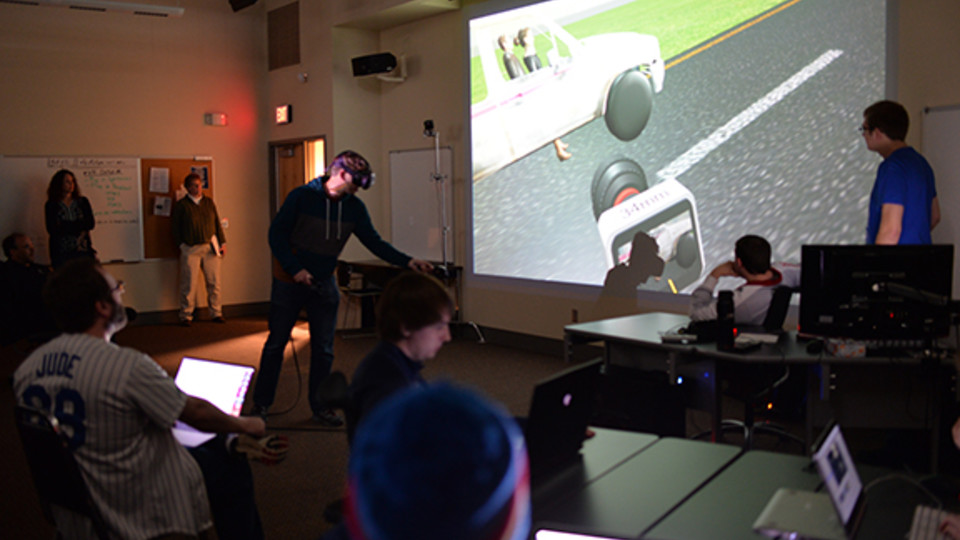 Ben Hartzell (left, in virtual reality goggles), a senior film and new media major, shows the progress of his team's final project in class on April 10.