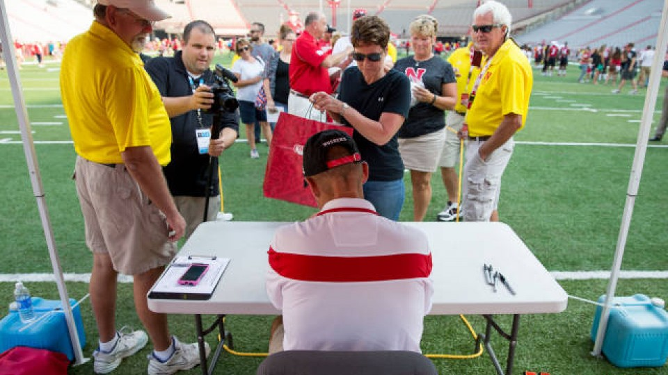 Nebraska head coach Mike Riley signs an autograph during UNL's 2015 Fan Day at Memorial Stadium.