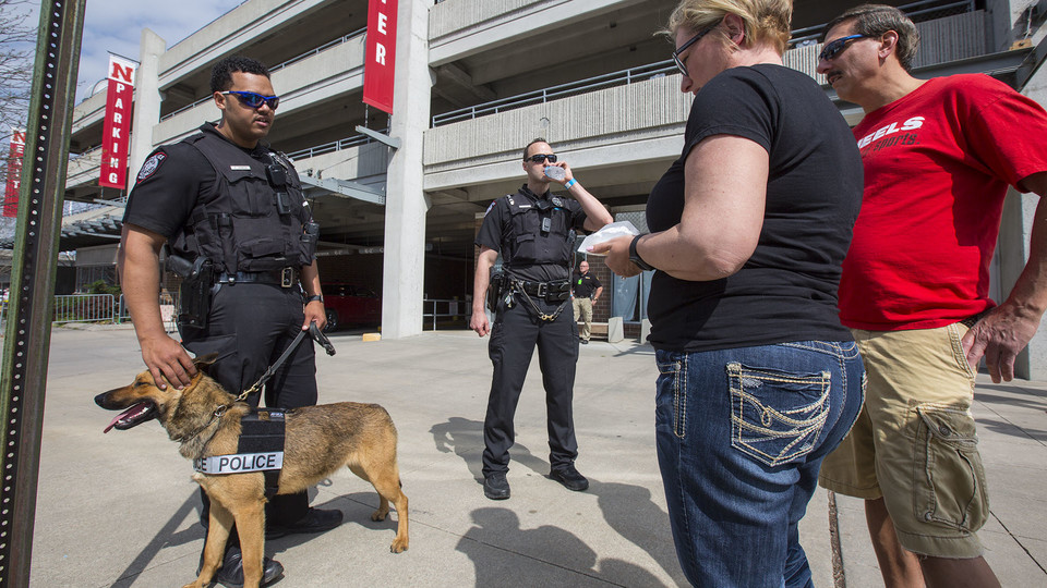 Nebraska K-9 officers Russell Johnson Jr. (left) and Greg Byelick talk with Husker fans prior to the Husker football spring game on April 15. The University Police Department has launched a new effort to expand outreach to the campus community.