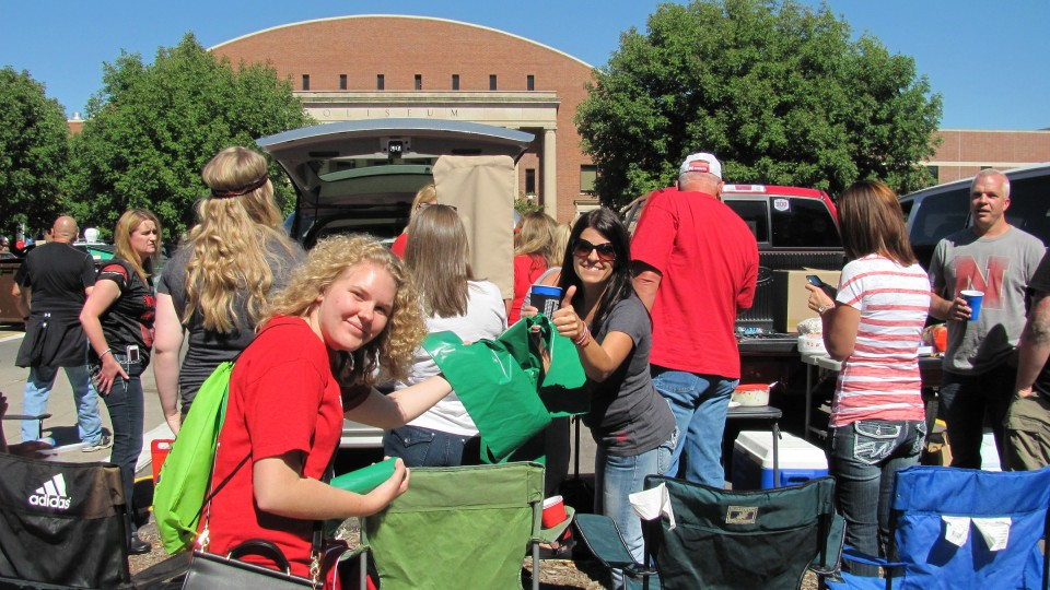 "A volunteer from the ""Go Green for Big Red"" hands out a recycling bag during a Husker home football game. Volunteers are being sought for the 2016 season."