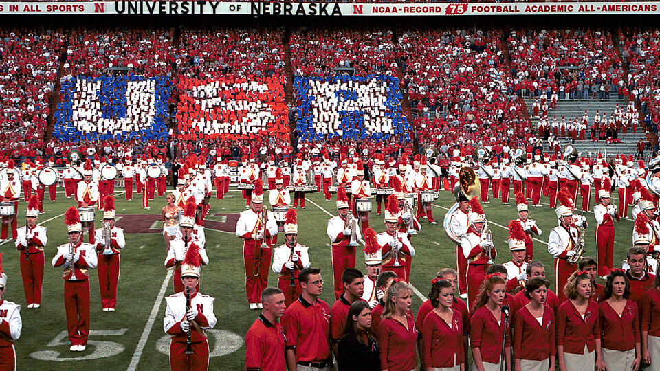 """Band members and singers stand on the Memorial Stadium turf as fans lift red, white and blue cards to spell out """"USA"""" during Sept. 20, 2001 pregame activities."""