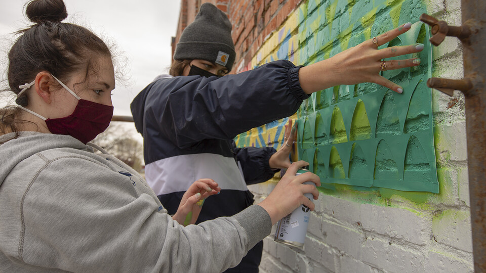 Honors students (from left) Sophie Newman and Ellie Hellman spray paint a stencil as part of the mural project in Lincoln's historic Havelock neighborhood on April 17. Students paired up to create designs for the quilt-block mural.