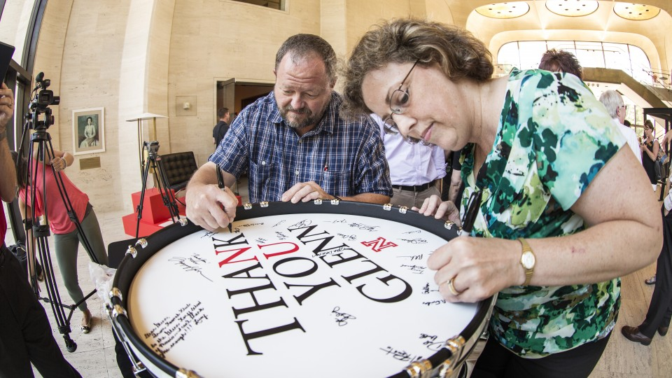 John Bailey and Gretchen Foley sign a bass drum during the Aug. 20 celebration of an $8 million gift by Glenn Korff. The drum was a gift for Korff.
