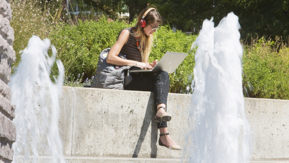 A UNL student stays cool near Broyhill Fountain on Monday. Temperatures this week are expected to be very hot -- mid- to upper 90s through at least Saturday.