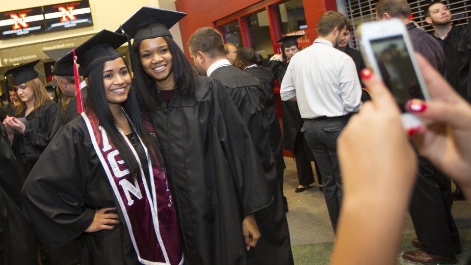 Lizzette Osorio (left) and Lea Henry pose for a photo before UNL commencement at Pinnacle Bank Arena on Dec. 21, 2013. A report issued by the Education Trust group showed that UNL is a national leader in improving graduation rates for underrepresented students.