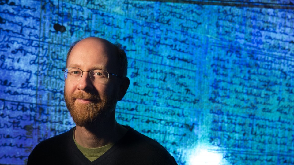 drian S. Wisnicki, assistant professor of English,  stands in front of a projected image of Dr. David Livingstone's  1871 diaries made readable using spectral imaging technology.