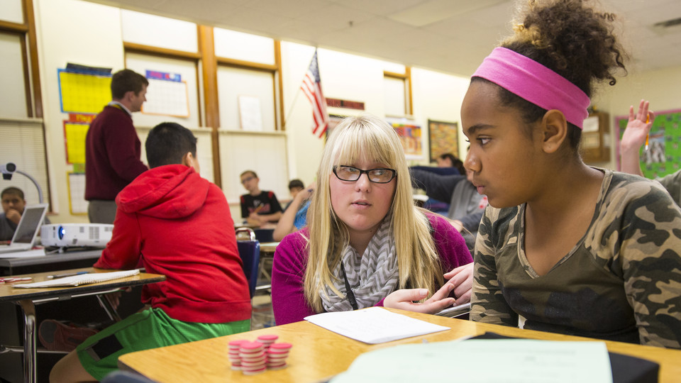 Megan Jorgensen, a Nebraska student teacher in 2014, works with a sixth grader at Park Middle School. A university research team is examining how experienced educators can act as coaches, providing feedback to teachers and enhance classroom performance.