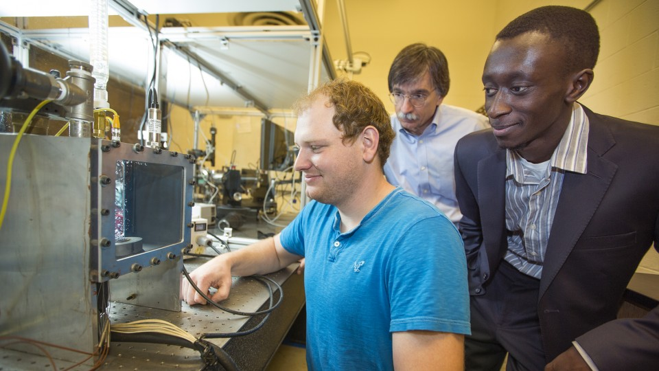 Corey Kruse, (from left) an engineering graduate student, shows a part of his research to faculty members George Gogos and Sidy Ndao. Kruse received a 2014 NASA Space Technology Research Fellowship.