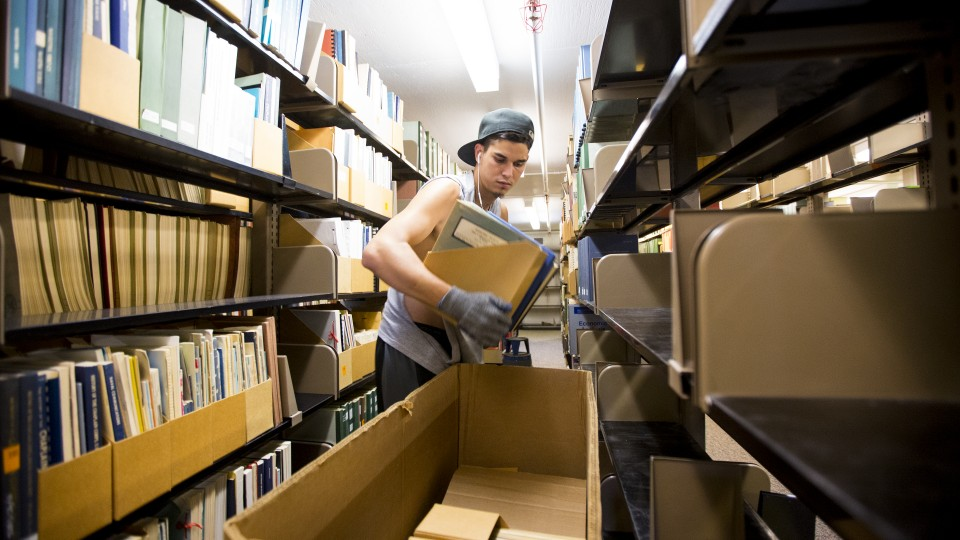 Jonny Reico with VonRentzell Movers packs books in the third floor stacks of Love Library South as part of the Learning Commons Project. Work on the project started in July.