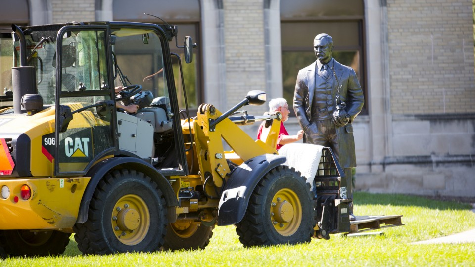 Workers use a tractor to position the new life-sized sculpture of J. Sterling Morton on East Campus on Sept. 8. The sculpture is one of four honoring Nebraskans who have served as U.S. Secretary of Agriculture.