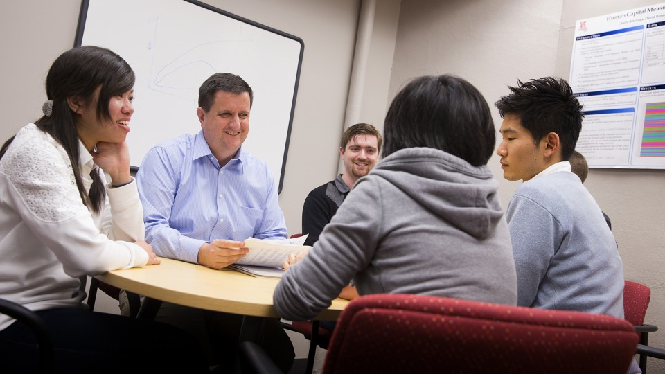 Eric Thompson (second from left), associate professor of economics and head of the Bureau of Business Research, works with student research assistants.