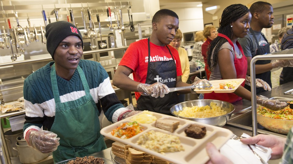 SUSI students (from left) lbinasio (Angola), Mzingaye (Zimbabwe), Kama (Angola) and Mompati (Botswana) help serve lunch at the Matt Talbot Kitchen on Jan. 27.