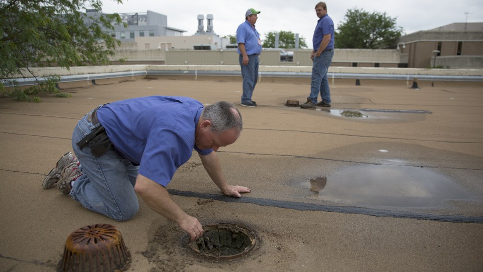 Bryan Ludemann (left) removes debris from a roof drain as Scott Hunt (right) and Scott Blair discuss possible roof repairs to UNL's Life Sciences Annex on East Campus. Spring rains have created a variety of unique challenges for UNL building systems maintenance employees.