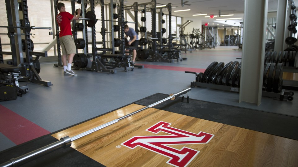 UNL students and Campus Recreation employees (from left) Joe Grobeck and Nate Morhardt place weights on a compound rack in the new East Campus Recreation and Wellness Center. The new $14.89 million facility will host open houses July 8-10 before opening July 13.