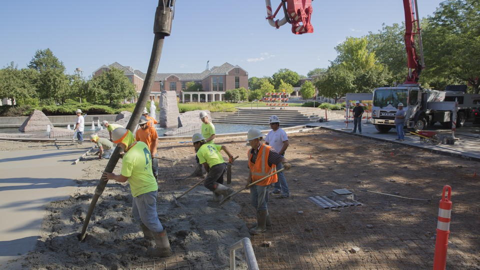 A crew of nearly 20 construction workers work concrete poured in the Union Plaza on City Campus on July 31. UNL schedules most concrete replacement projects between early July and late August, which is a time when there is less activity on campus.
