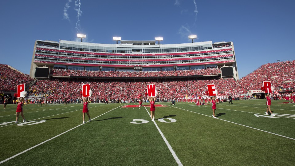 Nebraska cheerleaders take the field for a Husker Power cheer prior to the 2015 homecoming game in Memorial Stadium. Homecoming week activities this year culminate in the Huskers' game with IIllinois on Oct. 1.