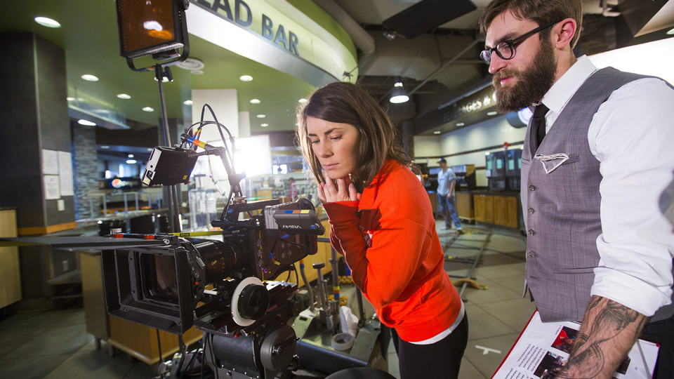 """Nebraska's Amanda Christi and Andrew Swenson film a recruitment video in the Abel-Sandoz Dining Center. The admissions duo also led Nebraska's production of the """"In Our Grit, Our Glory"""" institutional spot."""