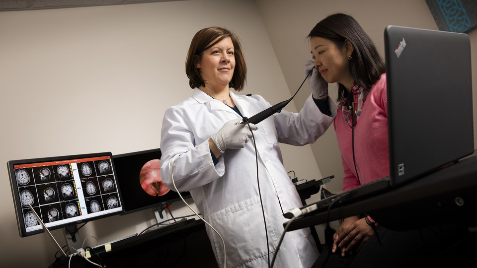 Angela Dietsch uses a scope to image a client's throat in her lab in the Barkley Memorial Center. Dietsch, an assistant professor of special education and communication disorders, is among faculty who have earned national awards in recent years, having been selected for an American Speech-Language-Hearing Association Early Career honor.