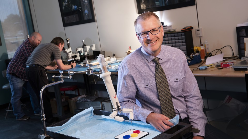 Shane Farritor has been named a Fellow of the National Academy of Inventors. He is pictured here with a prototype of one of his advanced miniaturized robots that shows promise for colon resection, a procedure used to treat diverticulitis, large colon polyps, precancerous and cancerous lesions of the colon and inflammatory bowel disease.