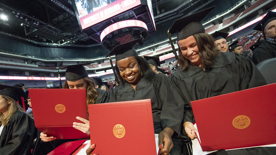 Nebraska grads examine their diplomas during a commencement exercise in Pinnacle Bank Arena. Graduates who have lost diplomas due to spring floods can get them replaced at no cost through a partnership between the Nebraska Alumni Association and University Registrar.