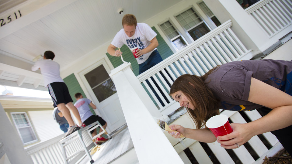 Kate Christensen from Utah works on a porch rail while her husband, L1 law student Theron Christensen works on the porch column at a house on B Street. Students, faculty and staff from the College of Law participated in the city-wide Paint-A-Thon by painting four houses. August 20, 2016.