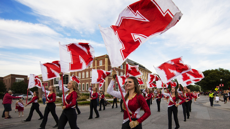 Cornhusker Marching Band flags fly along R Street during the 2016 homecoming parade