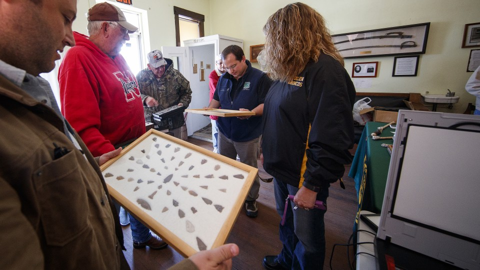 Dennis Kuhnel (center) and Matt Douglass look over a collection brought in by Chuck Anders (in the Husker sweatshirt), and his daughter Jennifer Peters (right), during the Artifacts Roadshow event on Oct. 7 in Mullen.